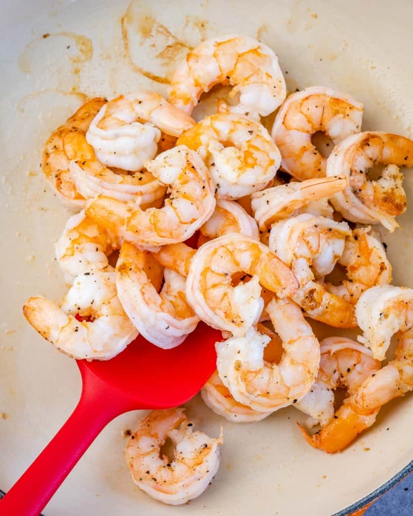 cooked shrimp in a pan with red spatula in it