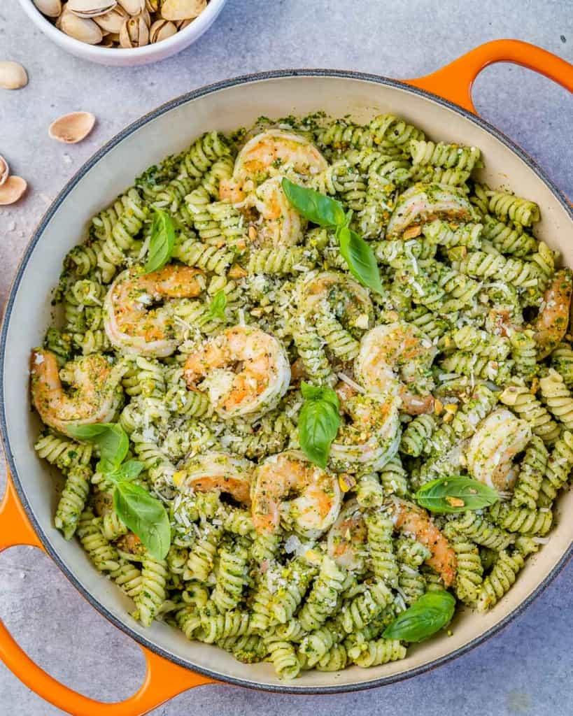 top view of pesto pasta in an orange skillet with shrimp