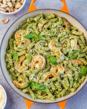top view of pesto pasta with shrimp in an orange skillet