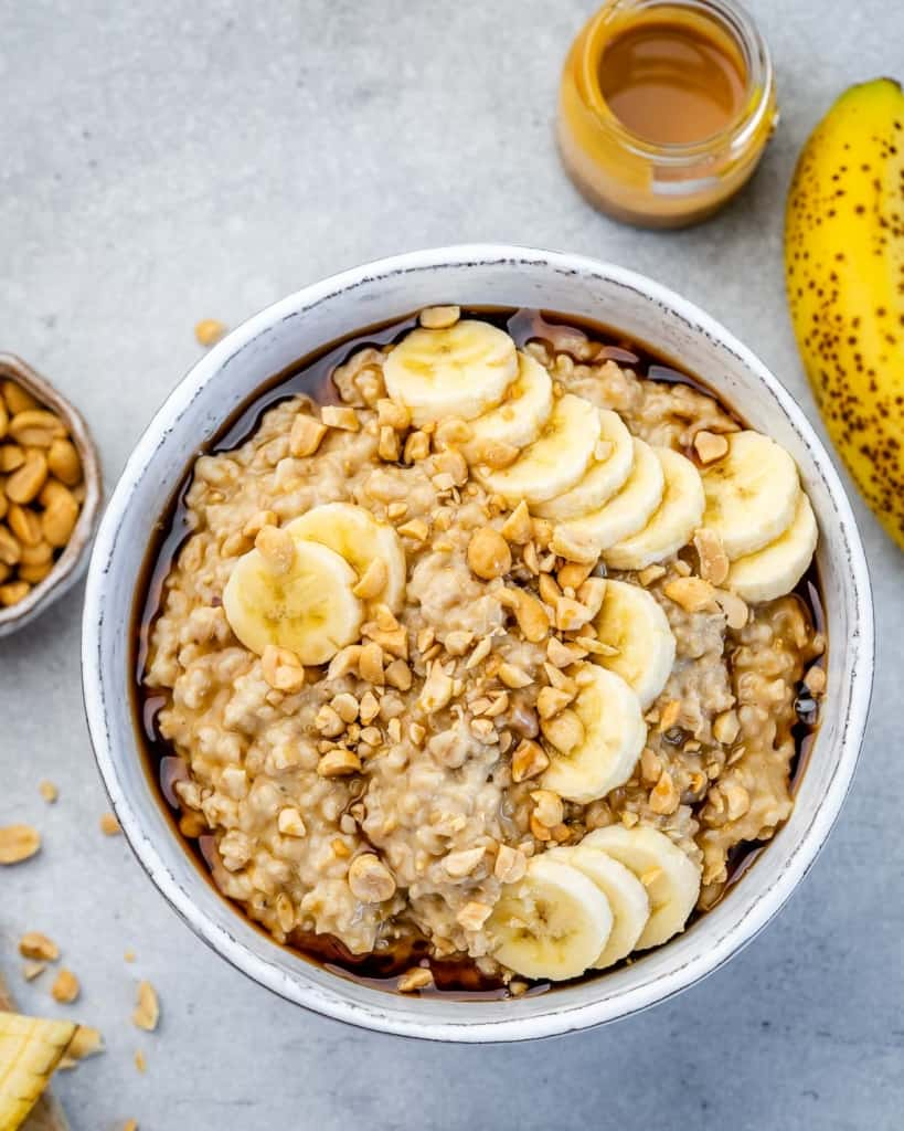 top view steel cut oatmeal in a white bowl topped with peanut butter, sliced bananas, and roasted peanuts