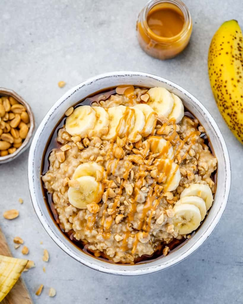 top shot view of oatmeal bowl with sliced bananas and peanut butter drizzle.