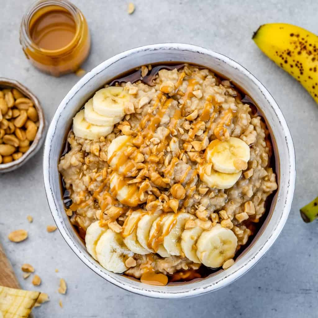 top view steel cut oats in a white bowl topped with bananas and peanut butter
