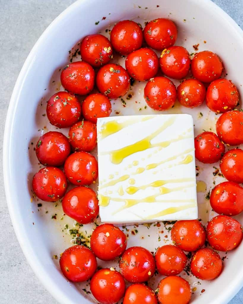 tomatoes around a block of feta cheese with olive oil drizzle