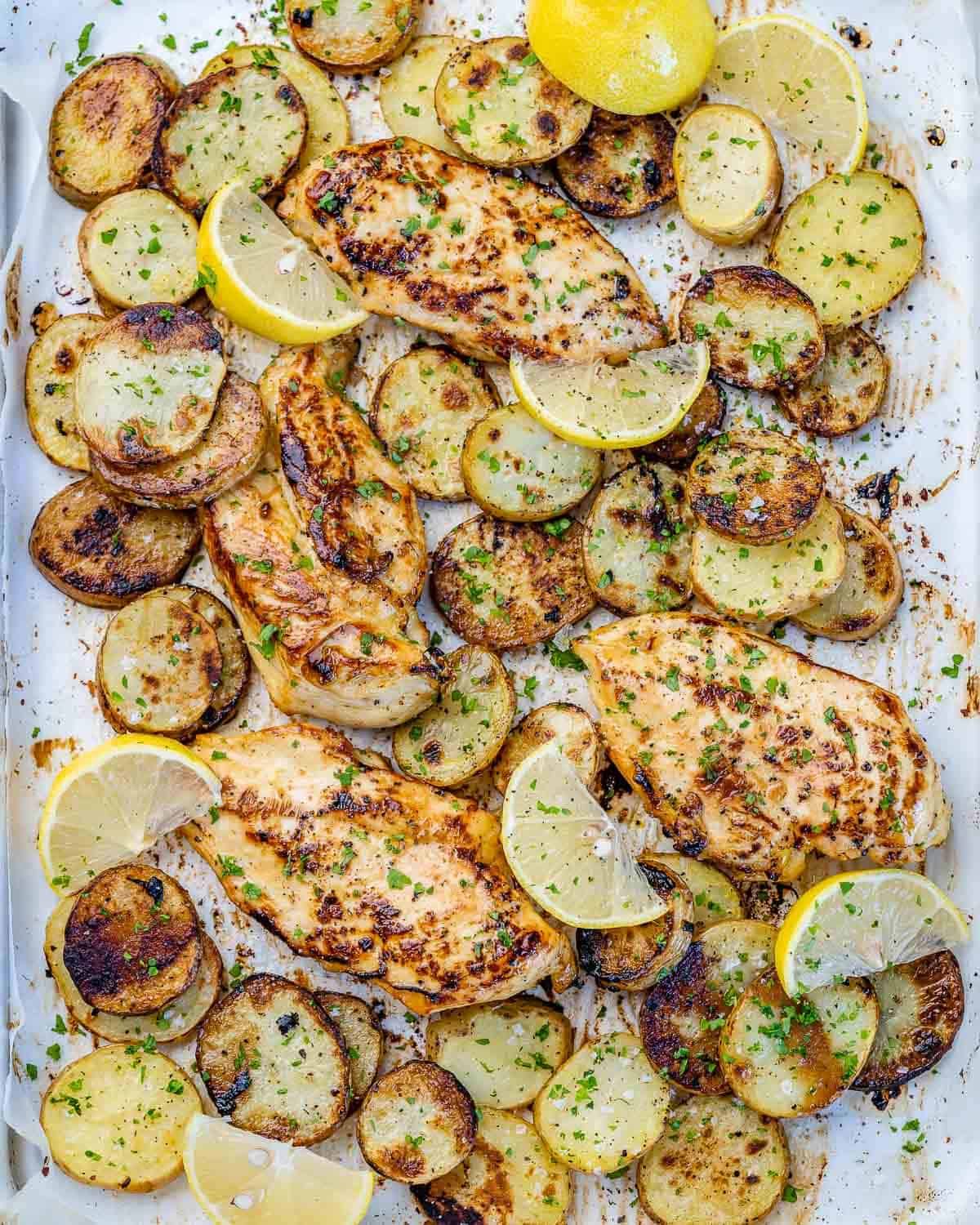 top view baked chicken breasts and potatoes on a sheet pan
