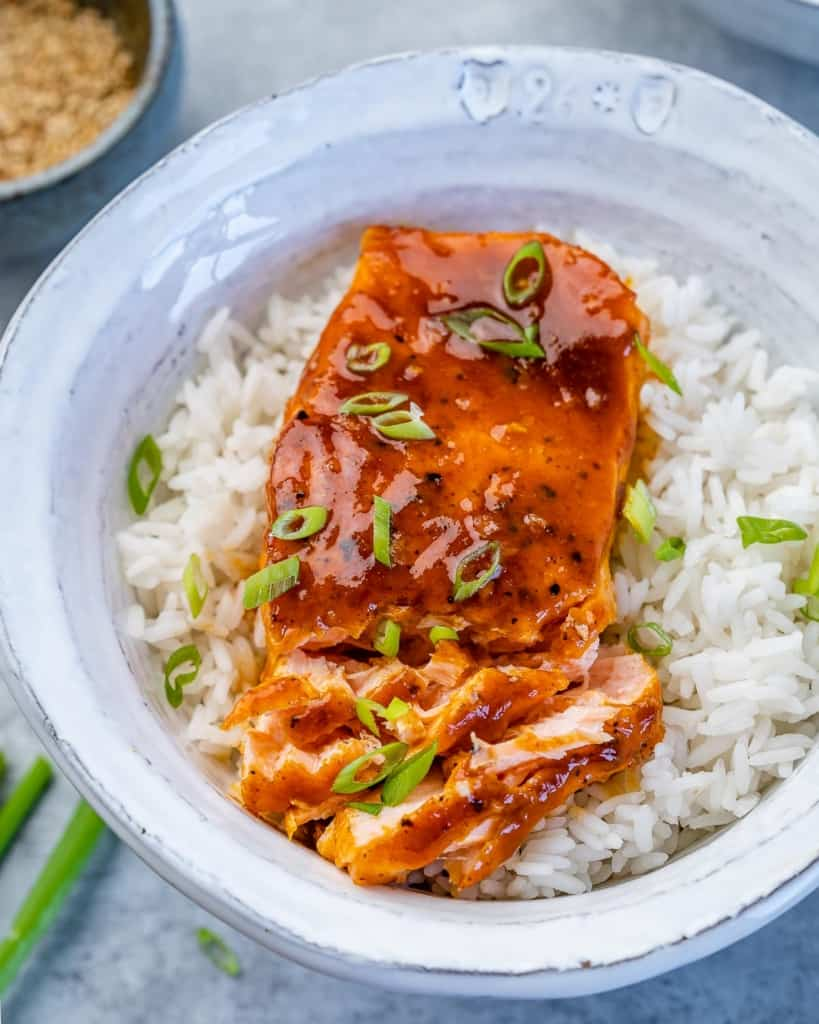 flaked baked honey salmon over white rice in a white bowl garnished with sliced green onions