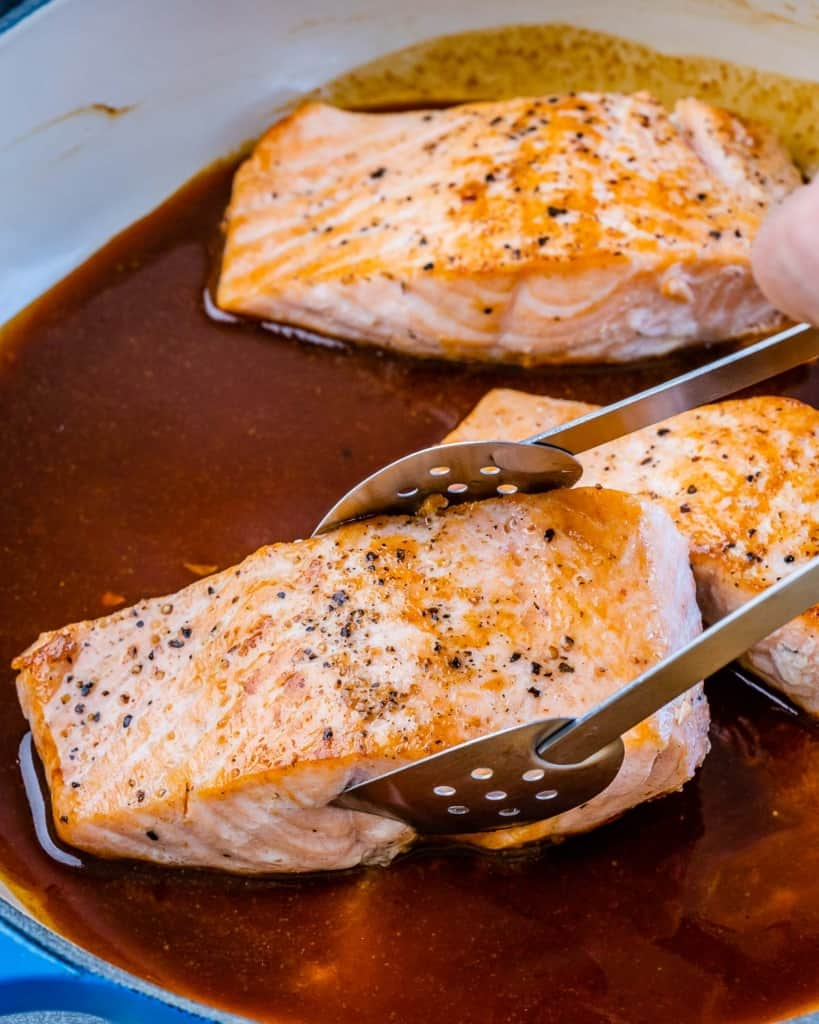 salmon filet being placed in honey glaze sauce