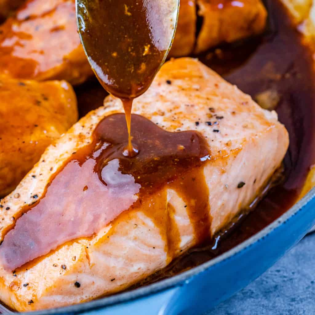 honey sauce being poured over salmon filet