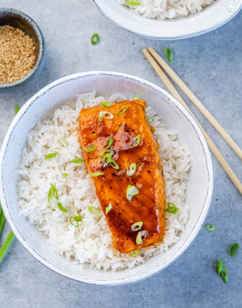 top view salmon filet over a bowl of rice garnished with green onions with chop sticks on the side
