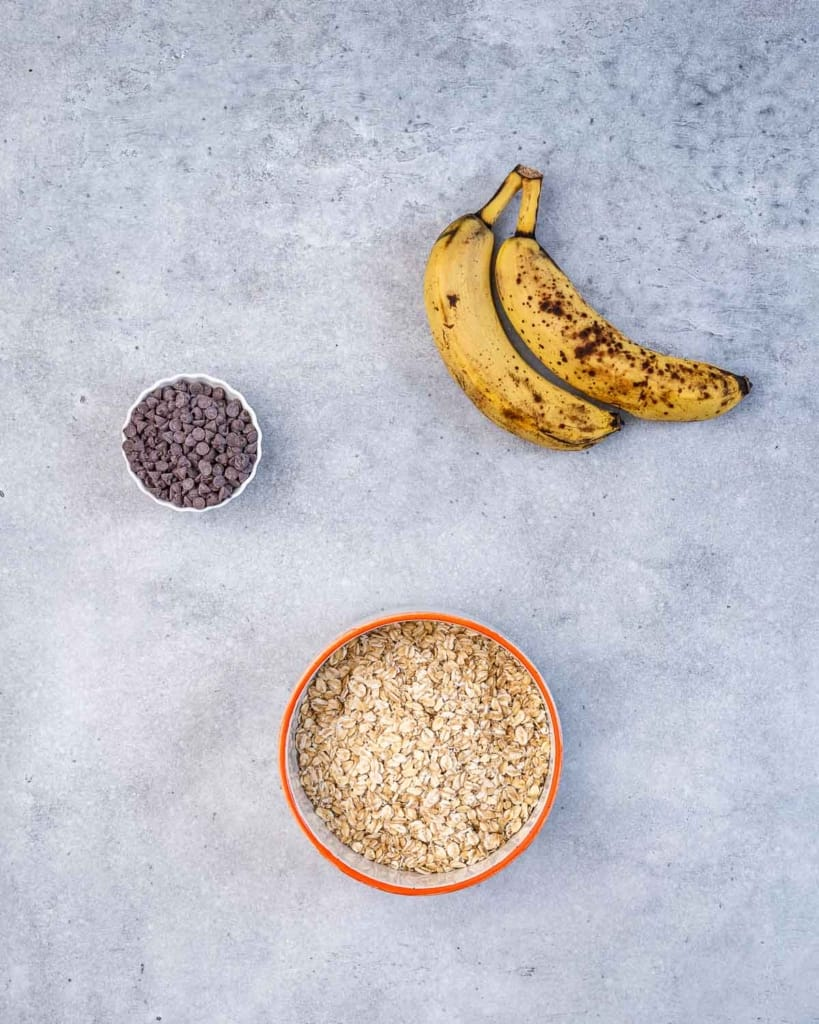 ingredients to make cookies. rolled oats in a bowl, chocolate chips, and 2 bananas