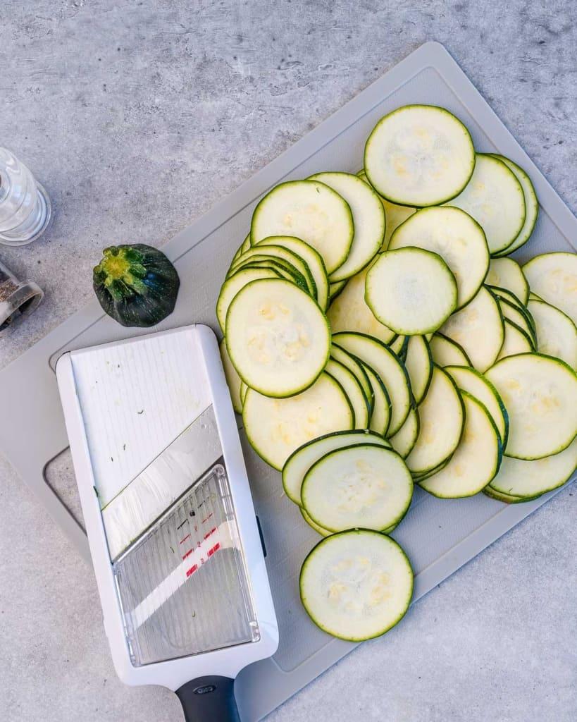 sliced zucchini next to mandolin on a cutting board
