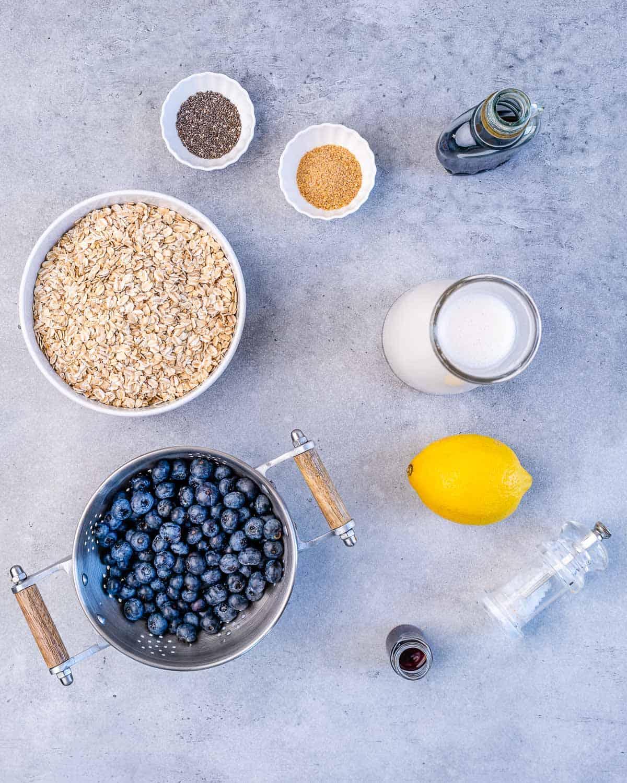 chia seeds, flax seeds, oats, lemon, milk, maple syrup, blueberries, salt, vanilla on grey surface