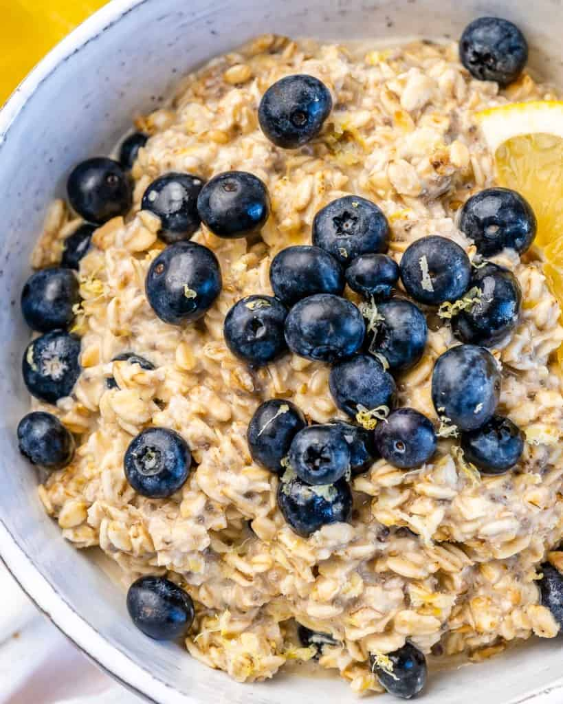 one bowl filled with oats topped with blueberries and lemon