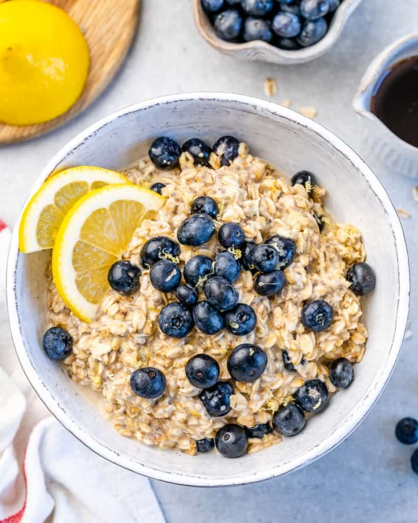 one bowl with overnight oats with blueberries and lemon wedges