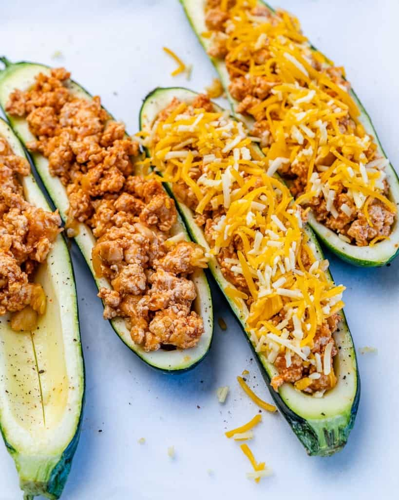 zucchini boats being stuffed with the buffalo chicken and topped with the shredded cheese