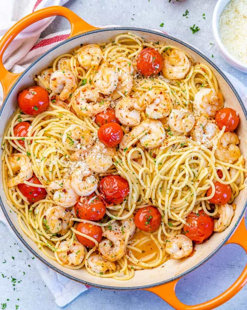 top view of shrimp pasta with cherry tomatoes in an orange skillet