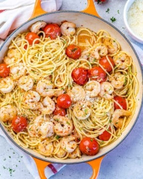 top view spaghetti with tomatoes and shrimp in an orange skillet