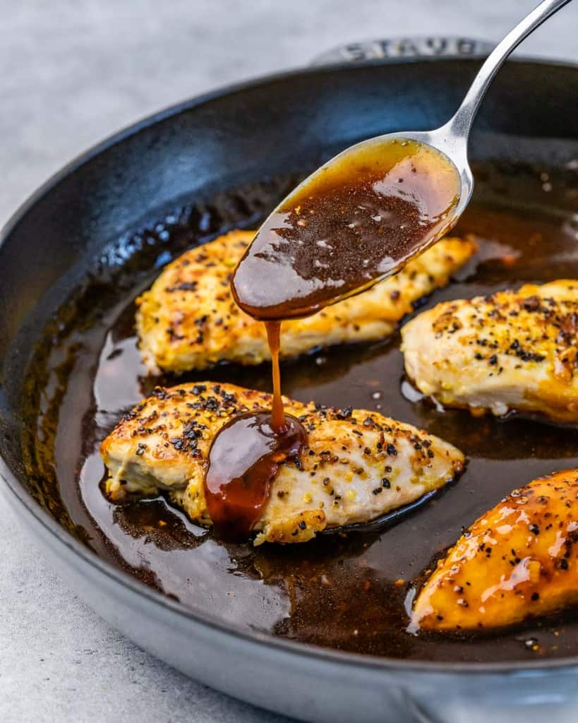 honey sauce being poured over chicken