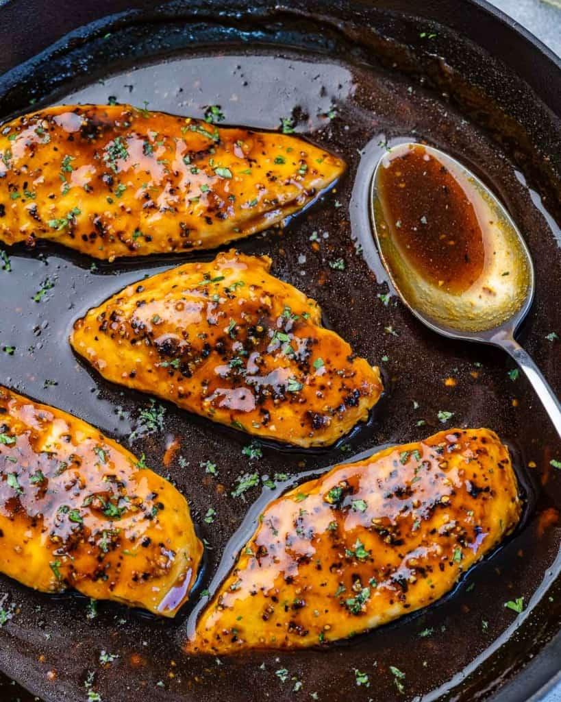 top view chicken breast in a honey garlic sauce in a black skillet