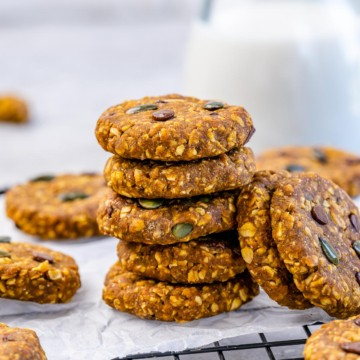 stacks of pumpkin cookies over a parchment paper on wire wrack