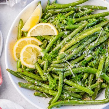 top view or roasted green beans topped with parmesan cheese and lemon garnishes
